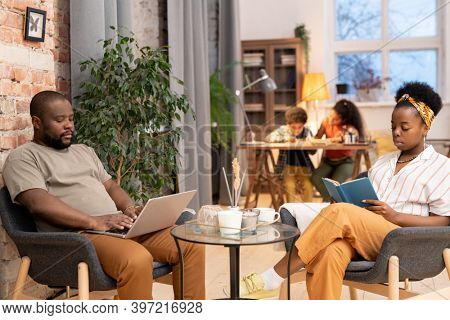 Young African woman reading book and her husband with laptop networking by small table while their kids doing homework