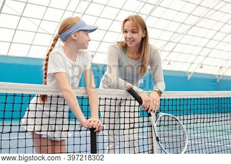 Cute blond girl in white sportswear and her trainer with tennis rackets leaning against net at stadium in front of camera and interacting