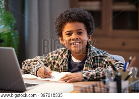 Cheerful little African schoolboy making notes in copybook and looking at you while sitting by table in front of laptop in home environment