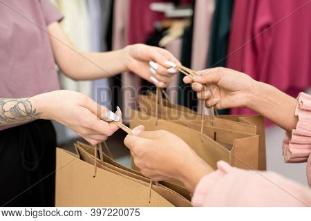 Hands of young female shop assistant passing big paperbags with new clothes to contemporary customer after payment for purchase