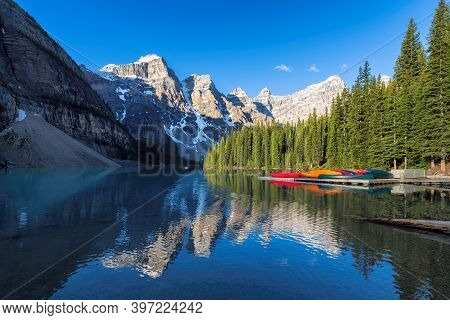 Beautiful Sunrise Over Turquoise Waters Of The Moraine Lake With Snow-covered Peaks Above It In Rock