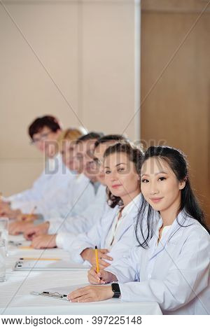 Group Of Researchers Taking Notes When Attending Meeting In Boardroom And Looking At Camera