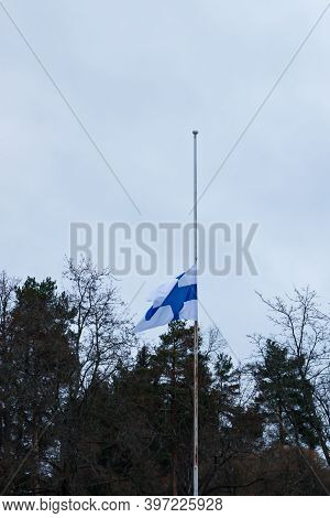 Finnish Flag Lowered To Half Mast On The Occasion Of Mourning At Cloudy Autumn Day