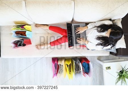 Woman Is Sitting On Couch At Home And Is Shopping Online. Black Friday Online Shopping Concept