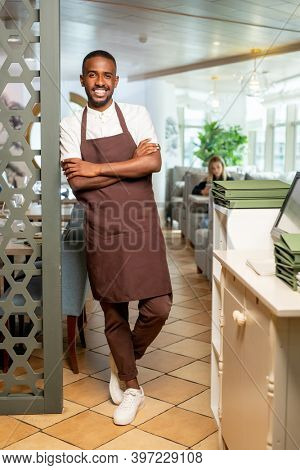Cheerful young African waiter in workwear leaning against armchair by served table inside luxurious restaurant while waiting for new guests