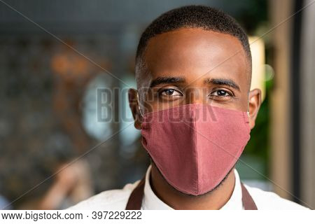 Head of young contemporary waiter of African ethnicity in protective mask standing in front of camera against cafe or restaurant interior
