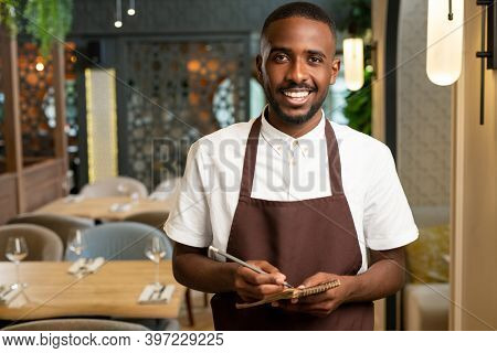 Happy young waiter with toothy smile holding pen and small notepad while standing in front of camera in restaurant and taking orders