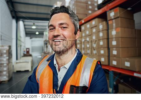 Close Up Of A Happy Factory Worker With Industrial Background