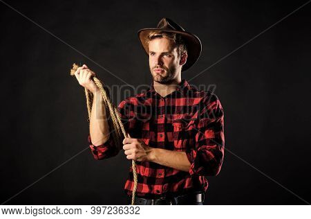 Brutal And Confident. Western Life. Man Unshaven Cowboy Black Background. Man Wearing Hat Hold Rope.