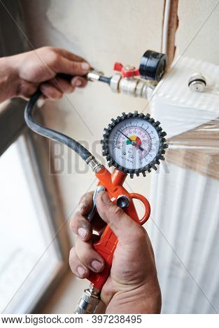Closeup Plumber Filling Pipes With Pressurized Air To Inspect For Leaks In New Heating System Instal
