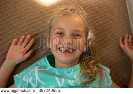 Portrait Of A Cheerful Girl Playing On The Floor In The Childrens Room, She Cheerfully Smiles At The