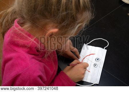 Little Girl Paints A Medical Mask. Draws On It A Smile And Eyes - A Funny Face. Pandemic
