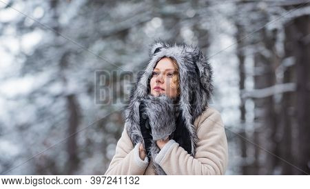 Girl In Snowy Forest. Faux Fur Animal Hat Perfect For Fantasy Theme. Heartwarming Concept. Animal Ca