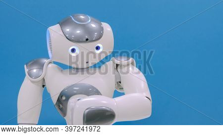 White Cute Robot Moving Hands And Head At Technology Exhibition. Robotic Future Concept