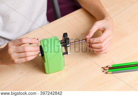 A Student Sharpens Pencils With A Sharpener. View From Above. Focus On Pencil And Hand.