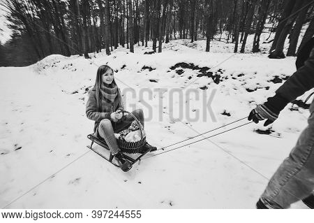 Happy Family: Man Carry Wooden Sledge With Girl On Sled Walking In Forest Outdoors. Walking On Holid