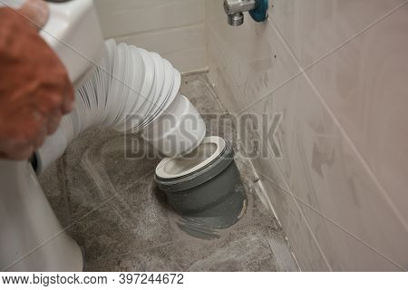 A Man Is Installing A Toilet Bowl Seat Connecting A Flexible Toilet Pan To A Soil Pipe, Waste Pipe W