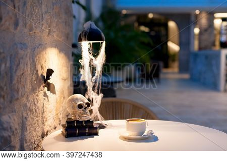 Halloween Decorations In Interior Of Hotel Lobby. Holiday Still Life With Cup Of Coffee, Skull, Book