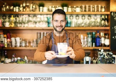 Shot Of Smiling Waiter Standing Behind The Counter And Holding A Cup Of Tea In His Hand.