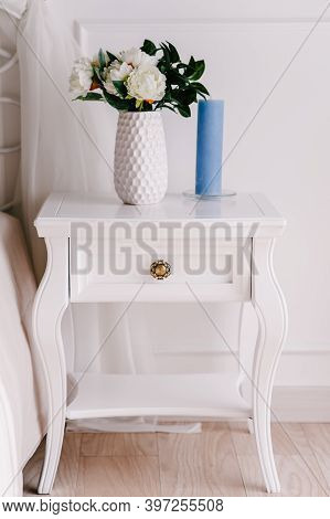 White Wood Bedside Table, Dresser In Bedroom. Bouquet On The Nightstand Vase With Flowers, Candle. I