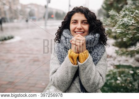 Smiling Young Woman Stands In A Frosty Snowy Winter Park. Female Wearing A Grey Coat And Blue Scarf