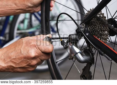 Bicycle Repair. Closeup of a bicycle derailleur and a mechanics hands making adjustments.