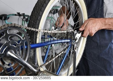 Bicycle Repair. Closeup of a mechanic tightening the rear wheel of a bike.