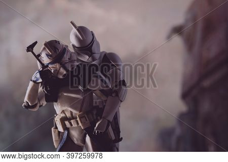 NOV 25 2020: scene from Star Wars The Clone Wars with Captain Rex carrying a wounded brother Clone Trooper during battle - Hasbro action figures