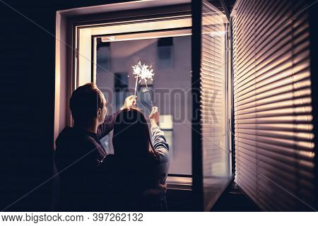 Couple Holding Sparklers Out Of The Window At Night. New Year's Eve Celebration, Anniversary, Party
