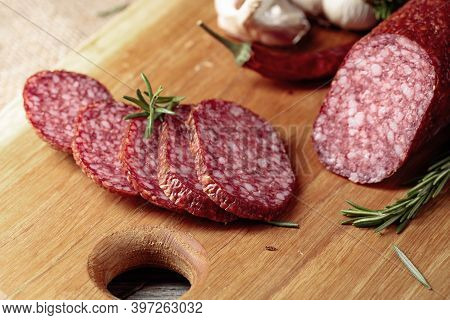 Salami On A Cutting Board. Sliced Sausage With Rosemary, Red Pepper, And Garlic On An Old Wooden Tab