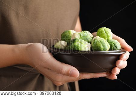 Woman Holding Bowl With Brussels Sprouts On Black Background, Closeup
