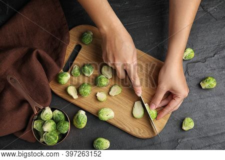 Woman Cutting Brussels Sprout At Black Slate Table, Top View