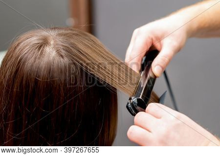 Hairdresser Straightens The Hair Of Woman With Hair Straightener Tool In A Hair Salon