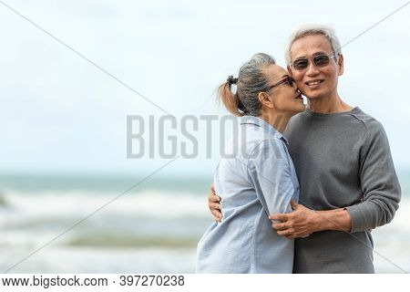Asian Lifestyle Senior Couple Hug And Kiss On The Beach Happy In Love Romantic And Relax Time. Peop