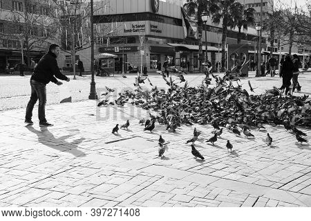 Izmir, Turkey - February 12, 2015: Man Feeds Pigeons On Konak Square In The Historical Central Part