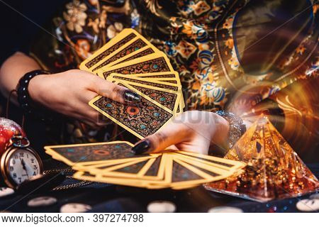 Astrology And Esotericism. A Fortune Teller Holds A Fan Of Tarot Cards. On The Table Are Runes And M