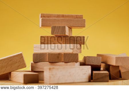 The Concept Of Entrepreneurial Risk With The Jenga Model. Wooden Blocks On A Yellow Background