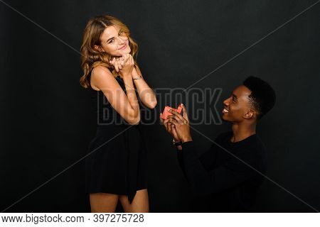 A Young Black Man Proposes To His Caucasian Girlfriend While Standing On One Knee. Multi-ethnic Coup