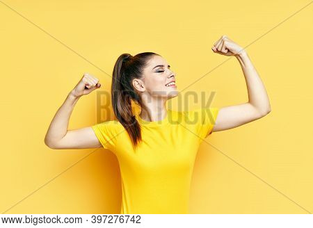 Powerful Confident Young Woman Showing Arms Muscles On Yellow Background. Woman Power. Confident And