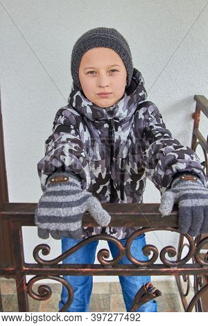 Boy Holding A Railing In Winter, Winter Gloved Boy Holding A Metal Handrail On The Stairs