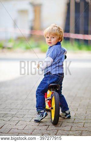 Active Blond Kid Boy In Colorful Clothes Driving Balance And Learners Bike Or Bicycle In Domestic Ga