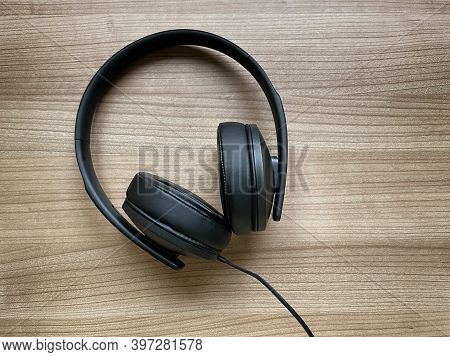 Pair Of Black Around-ear Or Over-ear Headphones Lying On Wooden Desk