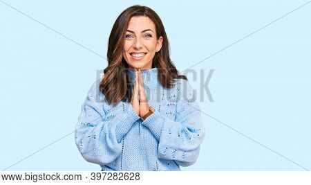 Young brunette woman wearing casual winter sweater praying with hands together asking for forgiveness smiling confident.