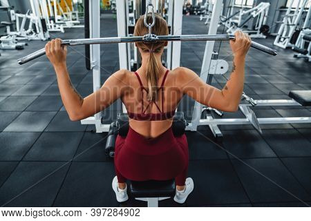 Caucasian athletic sportswoman doing exercise with fitness equipment while working out in gym