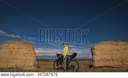 The Man Travel On Mixed Terrain Cycle Touring With Bikepacking. The Traveler Journey With Bicycle Ba