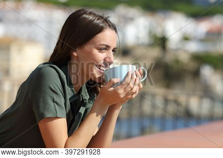 Happy Woman Drinking Coffee Contemplating Views In A Balcony On The Beach A Sunny Day