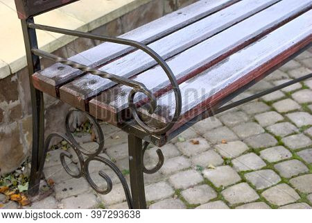 Openwork Forged Wooden Bench Handrail On The Background Of Paving Stones City Street Park Square Clo