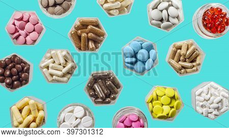 Medical Capsules And Pills In Hexagonal Jars On Blue Background