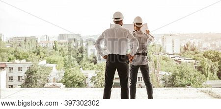 Back View Of Male Architects In Hardhats Examining Blueprint And Discussing Construction Project Whi