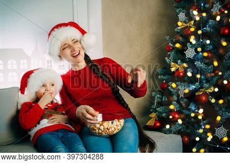 A Young Mother And Her Daughter In Santa Hats Watch Movies At Home For Christmas And Eat Popcorn
